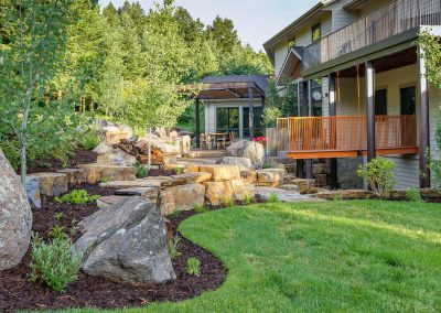 bozeman, belgrade and butte landscaping company designs of a home witih green grass, rockwork, and inset kitchen